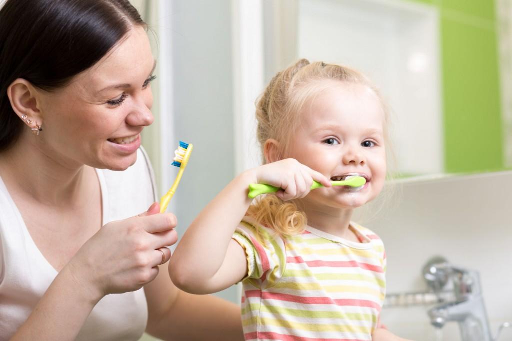 39038878 - cute mother teaching kid girl teeth brushing